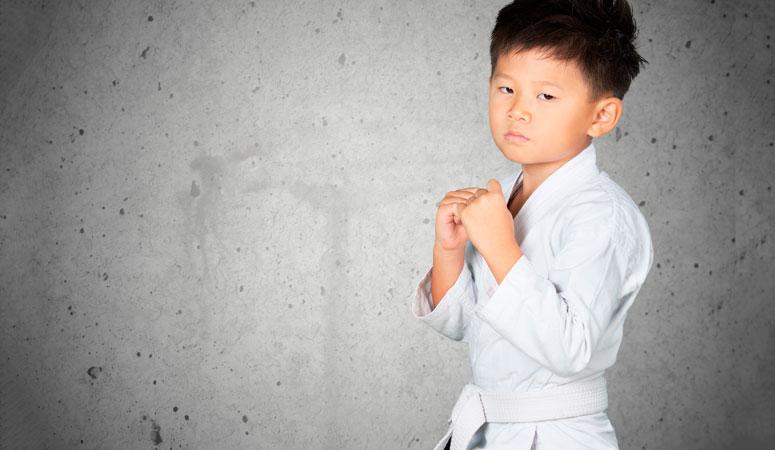 Menino vestido com kimono pronto para ação